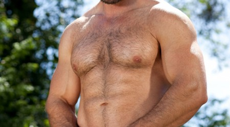 Hairy muscle man Brad Kalvo lowers his suit, revealing his hard tight butt