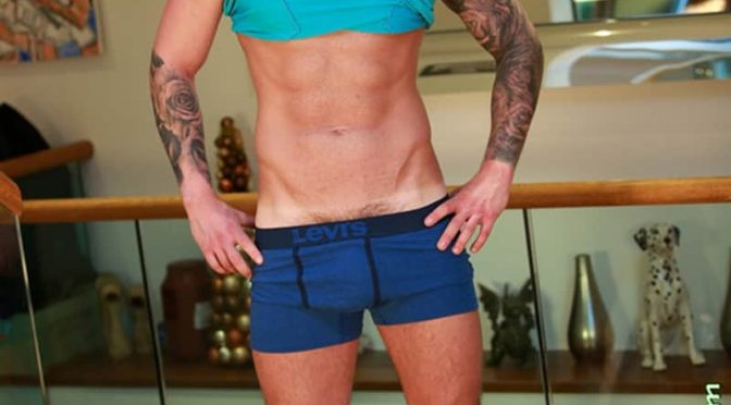 Ripped tattooed young muscle hunk Finian Morris strips down to his Levis underwear and jerks his huge uncut dick